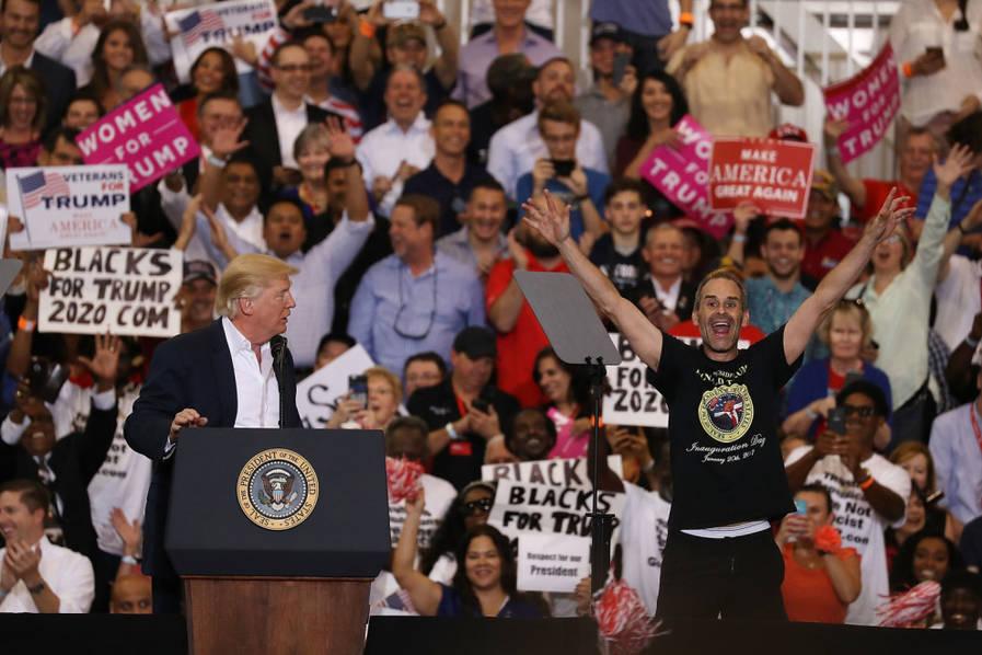 """在集会演讲过程中,特朗普突然停了下来,指着观众席第一排一名活跃的支持者说,""""瞧那家伙!快跳过防护栏到这里来,他能做到。""""特朗普邀请铁粉支持者与自己同台。"""