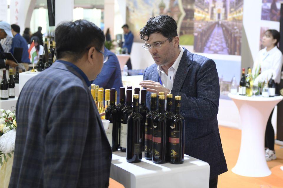4月13日,匈牙利参展商(右)在欧洲馆展区向观众推介匈牙利葡萄酒。新华社记者 黄宗治摄