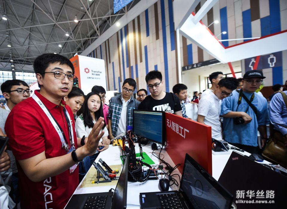 5月26日,工程师(前左)在数博会上向参观者介绍无人智慧工厂。   新华社记者 陶亮 摄