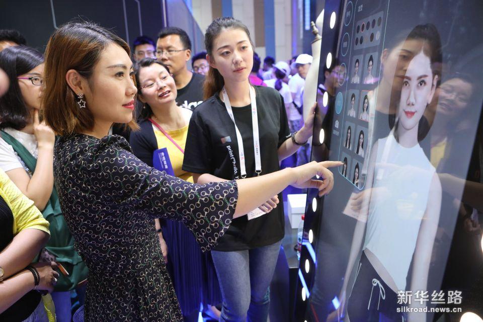 5月26日,参观者在数博会上通过阿里巴巴的虚拟试衣镜现场试衣。新华社记者 欧东衢 摄