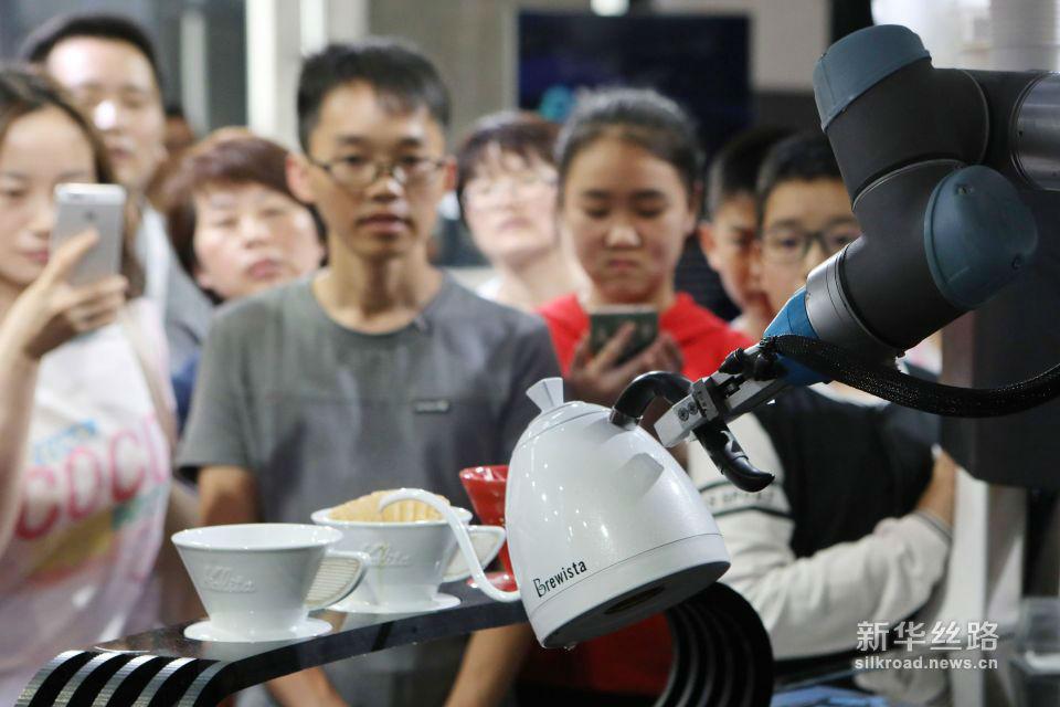 5月26日,参观者在数博会上观看机器摇臂制作手冲咖啡。新华社记者 欧东衢 摄