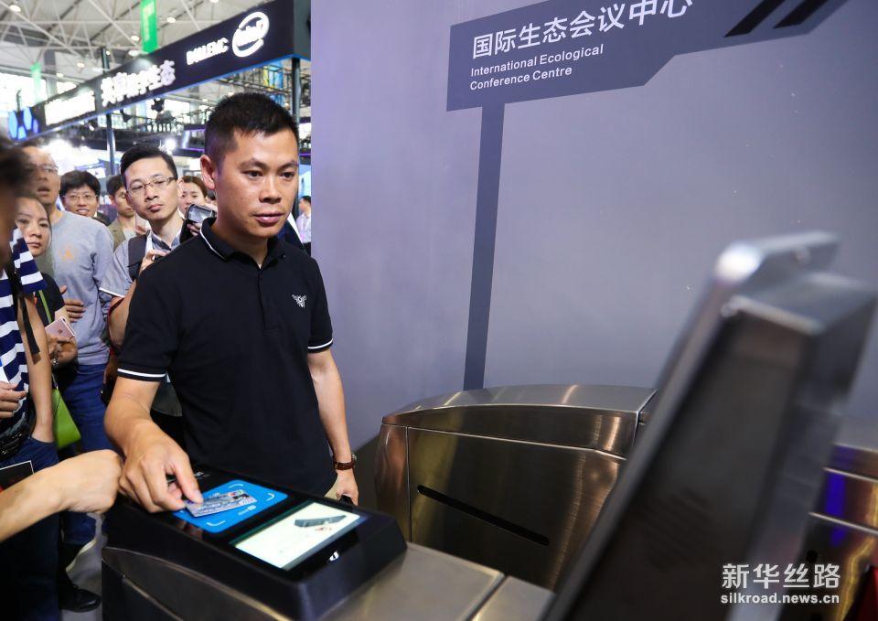 5月26日,观众在数博会上体验支付宝公交刷卡进站系统。新华社记者 刘续 摄