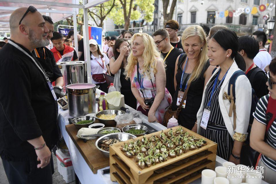 6月7日,市民和游客在现场准备品尝拉脱维亚美食。