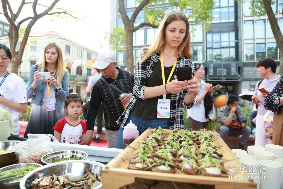 """中东欧友人在拍摄拉脱维亚美食""""熏鲱鱼黑麦面包""""。黄瑞鹏 摄"""