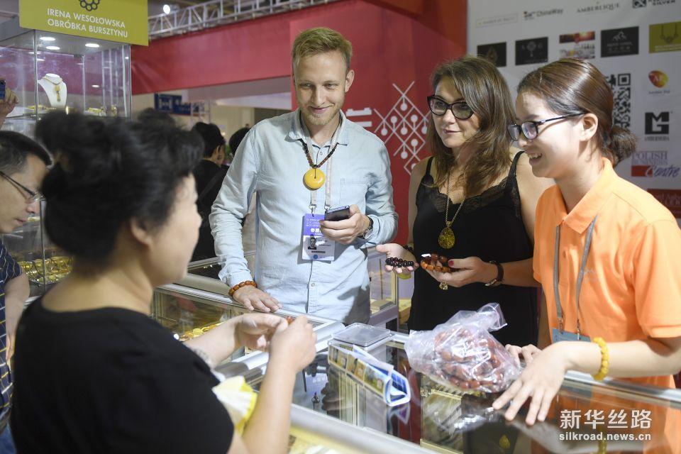 6月8日,参加中东欧商品展的波兰客商(中)向顾客展示波兰蜜蜡。新华社记者 黄宗治 摄