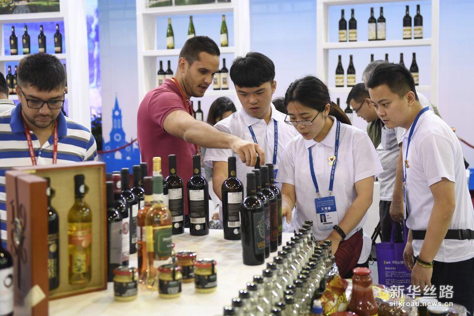 6月8日,参加中东欧商品展的客商现场展示来自保加利亚的红酒。新华社记者 黄宗治 摄