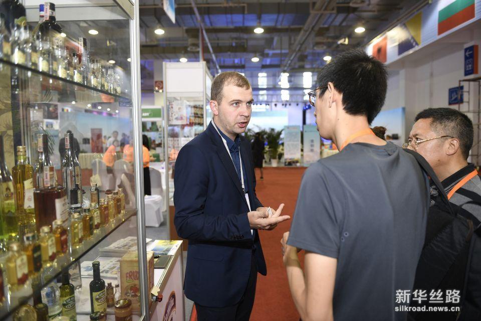 6月8日,参加中东欧商品展的客商向采购商介绍来自斯洛伐克的特色商品。新华社记者 黄宗治 摄