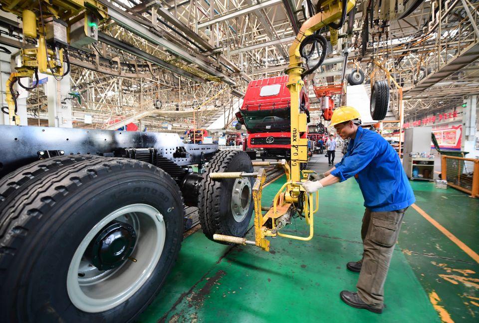 工人在陕重汽汽车总装配厂车间内安装轮胎(3月15日摄)。新华社记者 邵瑞 摄