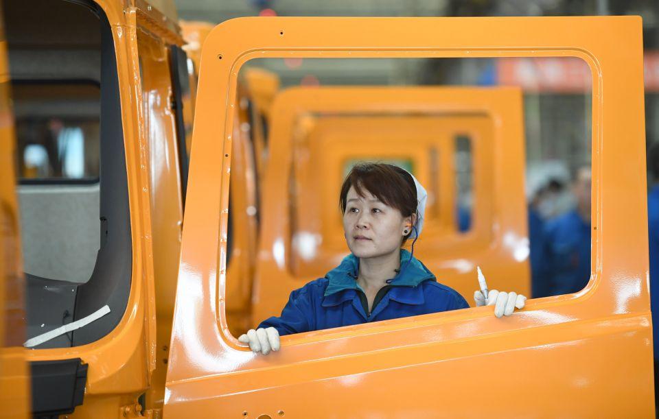 一名女工在陕重汽汽车总装配厂车间内检验驾驶室的装配质量(3月15日摄)。新华社记者 邵瑞 摄