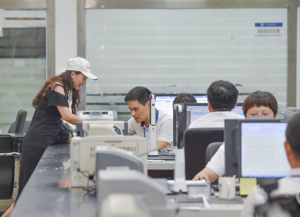 6月19日,市民(左)在福建省晋江市行政服务中心办理卫生许可证。新华社记者 宋为伟 摄