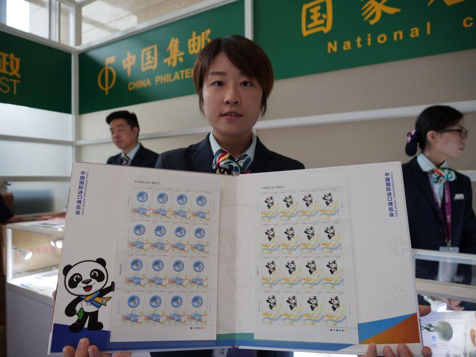 11月5日,一名邮政工作人员在国家会展中心(上海)新闻中心展示《中国国际进口博览会》纪念邮票首日封。新华社记者王益亮摄