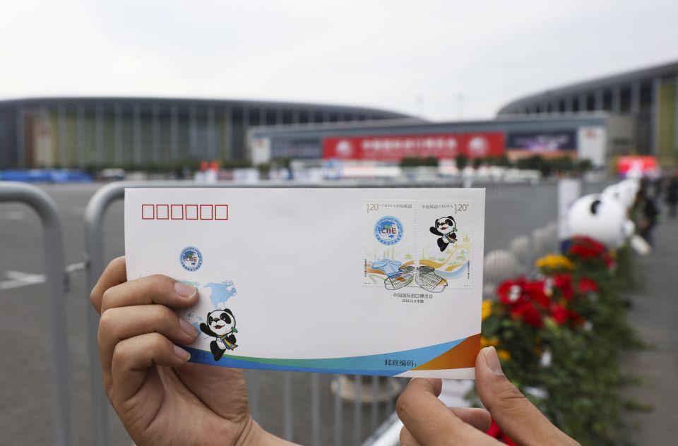 11月5日,一名媒体记者在国家会展中心(上海)前展示《中国国际进口博览会》纪念邮票首日封。新华社记者兰红光摄