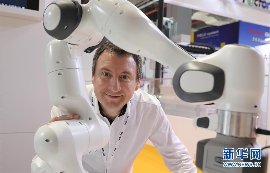 11月7日,德国福伊特公司的迈克尔·赫尔利在公司展台与产品合影。 新华社记者 方喆 摄