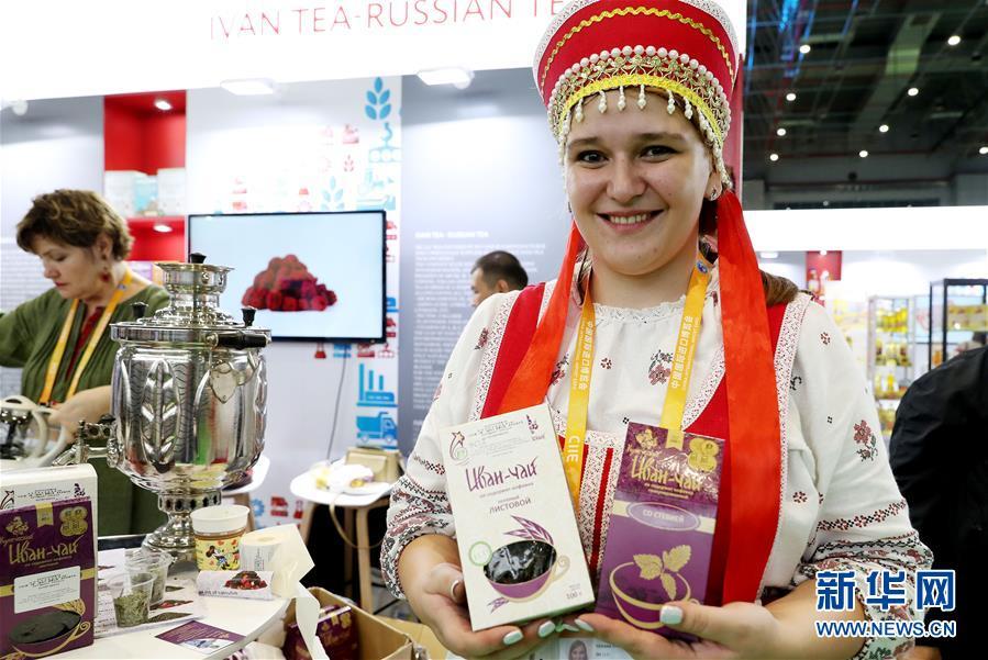 11月7日,来自俄罗斯的塔季扬娜·切尔卡申娜身着民族服装在展台上展示俄罗斯柳兰茶。 新华社记者 方喆 摄