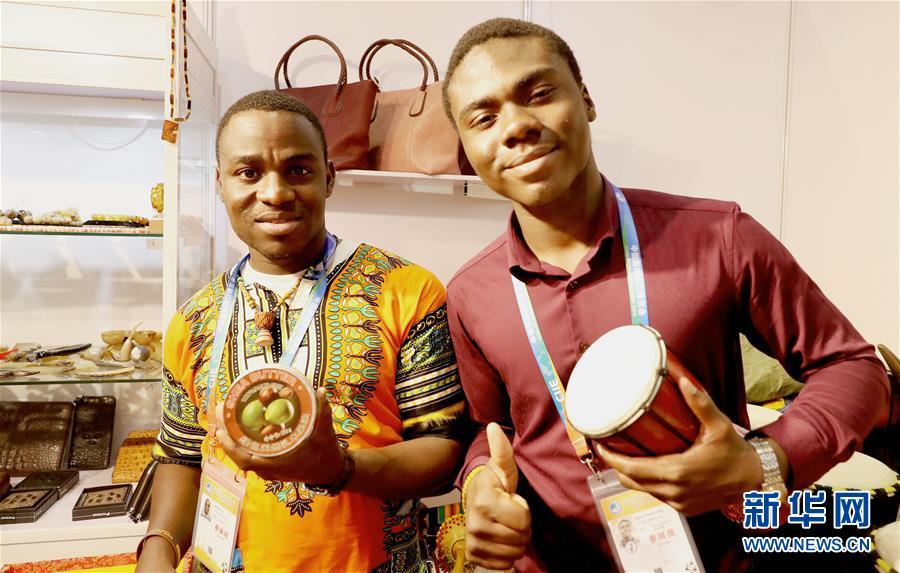 11月7日,中国非洲加纳商会的伯纳德(右)与同伴手持展品站在展台前。 新华社记者 方喆 摄
