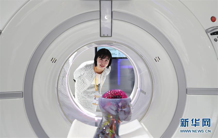 11月7日,美国通用电气医疗集团的刘西词站在公司生产的后超高端256排Revolution CT机后。 新华社记者 方喆 摄