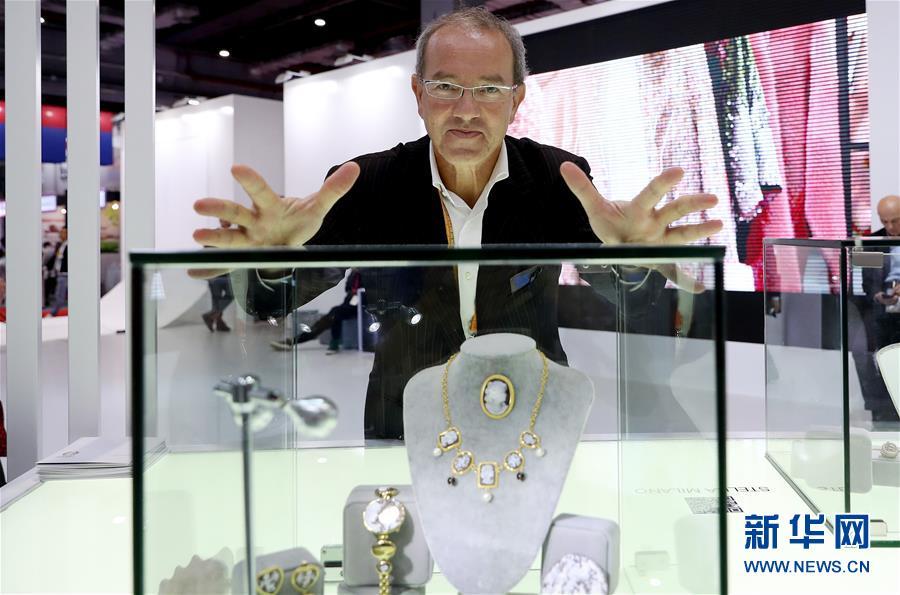 11月7日,意大利迪卢卡贝雕首饰公司的吉诺·迪卢卡站在自己设计的贝雕首饰展示柜前。在上海举行的首届中国国际进口博览会上,世界各地的人们带着自己的产品,在进博会大舞台上尽情展示。新华社记者 方喆 摄