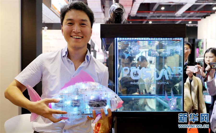 11月7日,韩国AIRO公司的刘沚炅手捧他的电子鱼产品站在展台上。 新华社记者 方喆 摄