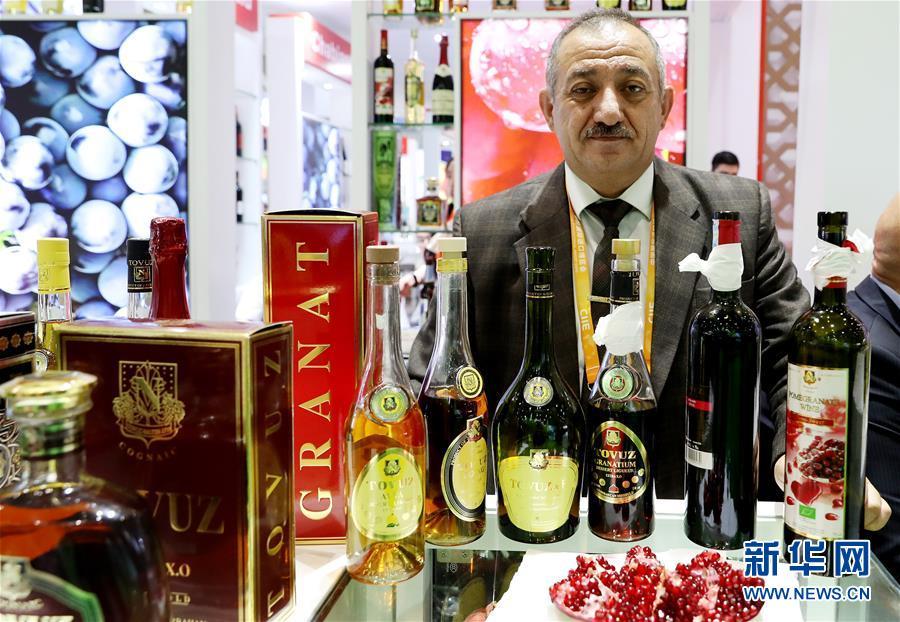 11月7日,来自阿塞拜疆的马马德利哈桑诺夫·阿里站在自己公司生产的酒类展品后。  新华社记者 方喆 摄