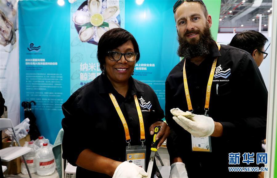 11月7日,来自纳米比亚的雅各布斯·亚伯拉罕·布洛乌(右)和保利娜·纳希拉展示产自纳米比亚的鲸湾翠蚝。  新华社记者 方喆 摄
