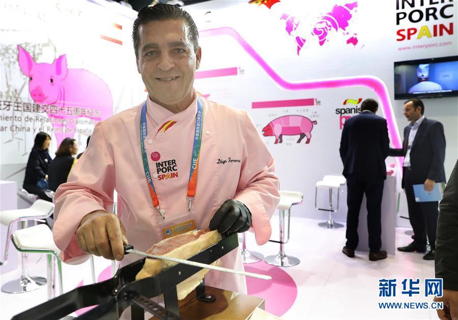 11月7日,来自西班牙的迭戈·费雷拉斯在展台上切割火腿。 新华社记者 方喆 摄