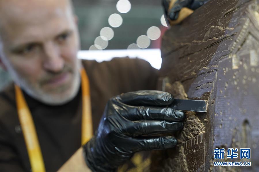 11月7日,在进博会食品及农产品展区,来自俄罗斯的巧克力雕塑家维塔利·波诺马廖夫在制作中国长城主题的巧克力雕塑作品。 新华社记者 沈伯韩 摄