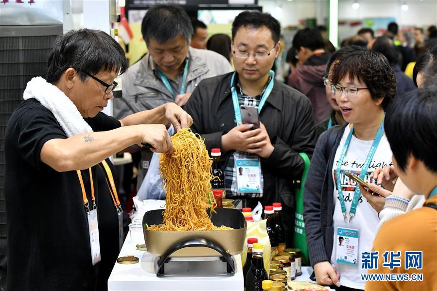 11月7日,来自新加坡广祥泰私人有限公司的工作人员用公司生产的调料为观众现场烹制炒面。 新华社记者 李鑫 摄