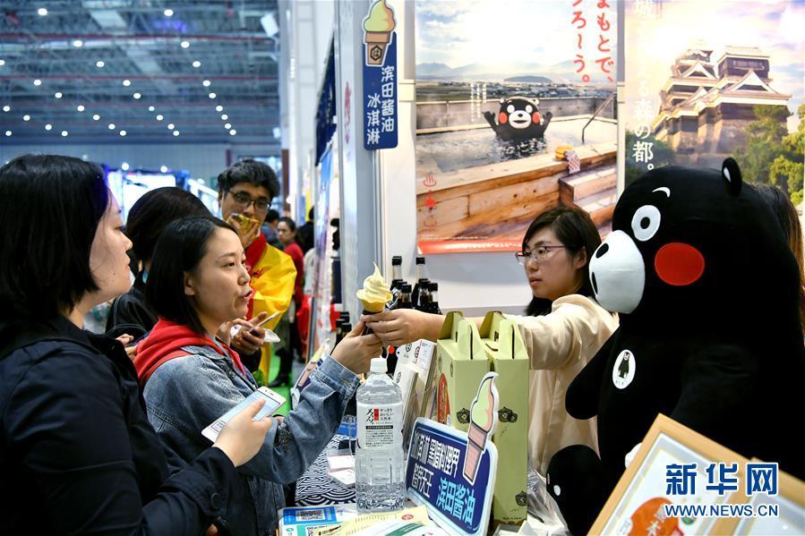 11月7日,观众在日本滨田酱油株式会社展台品尝酱油冰淇淋。  新华社记者 李鑫 摄