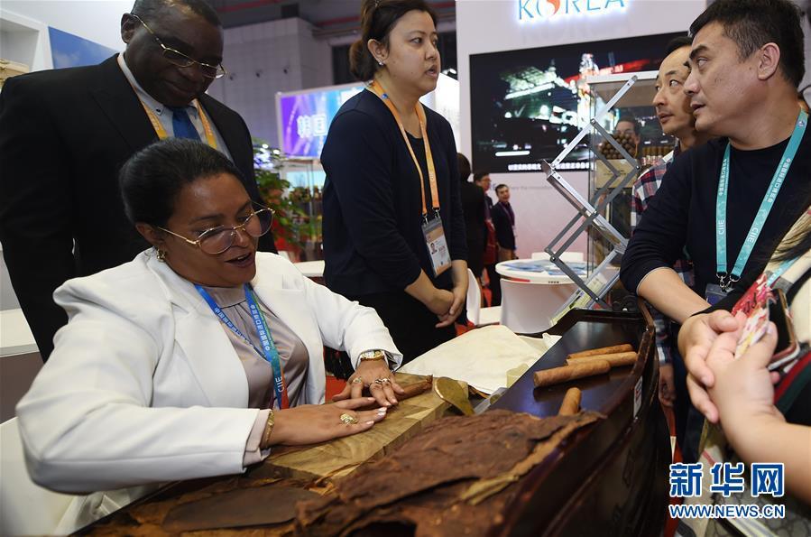 11月6日,来自古巴的工作人员在向参会者展示纯手工制作雪茄。 新华社记者 韩瑜庆 摄