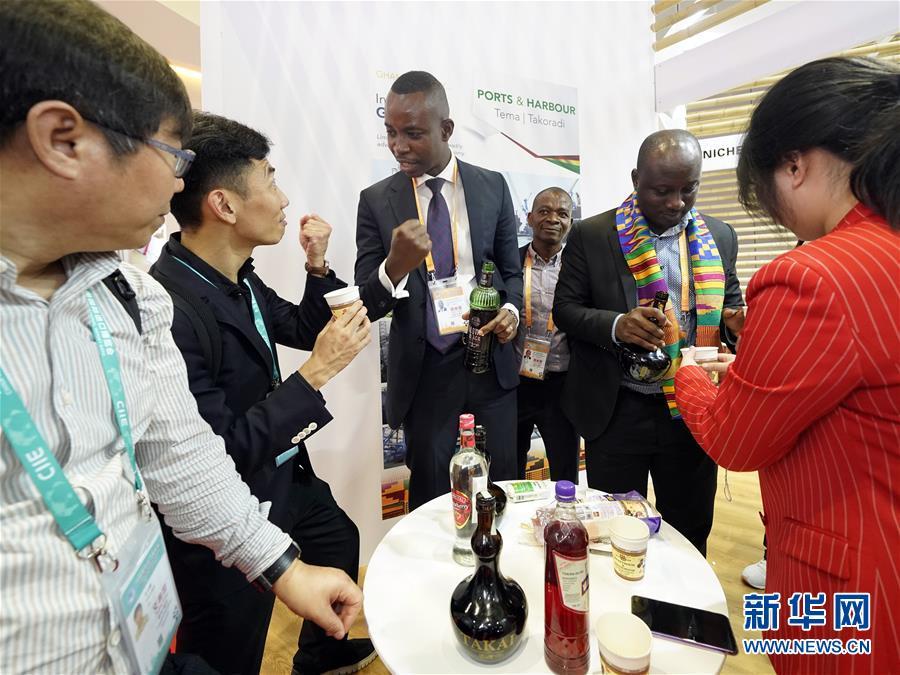 11月6日,来自加纳的工作人员在向参观者介绍用当地植物酿造的酒。 新华社记者 沈伯韩 摄