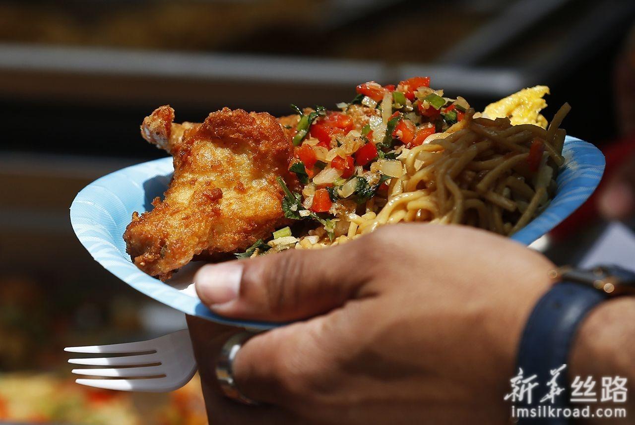5月18日,在美国洛杉矶,一名男子体验中国美食。新华社记者李颖摄