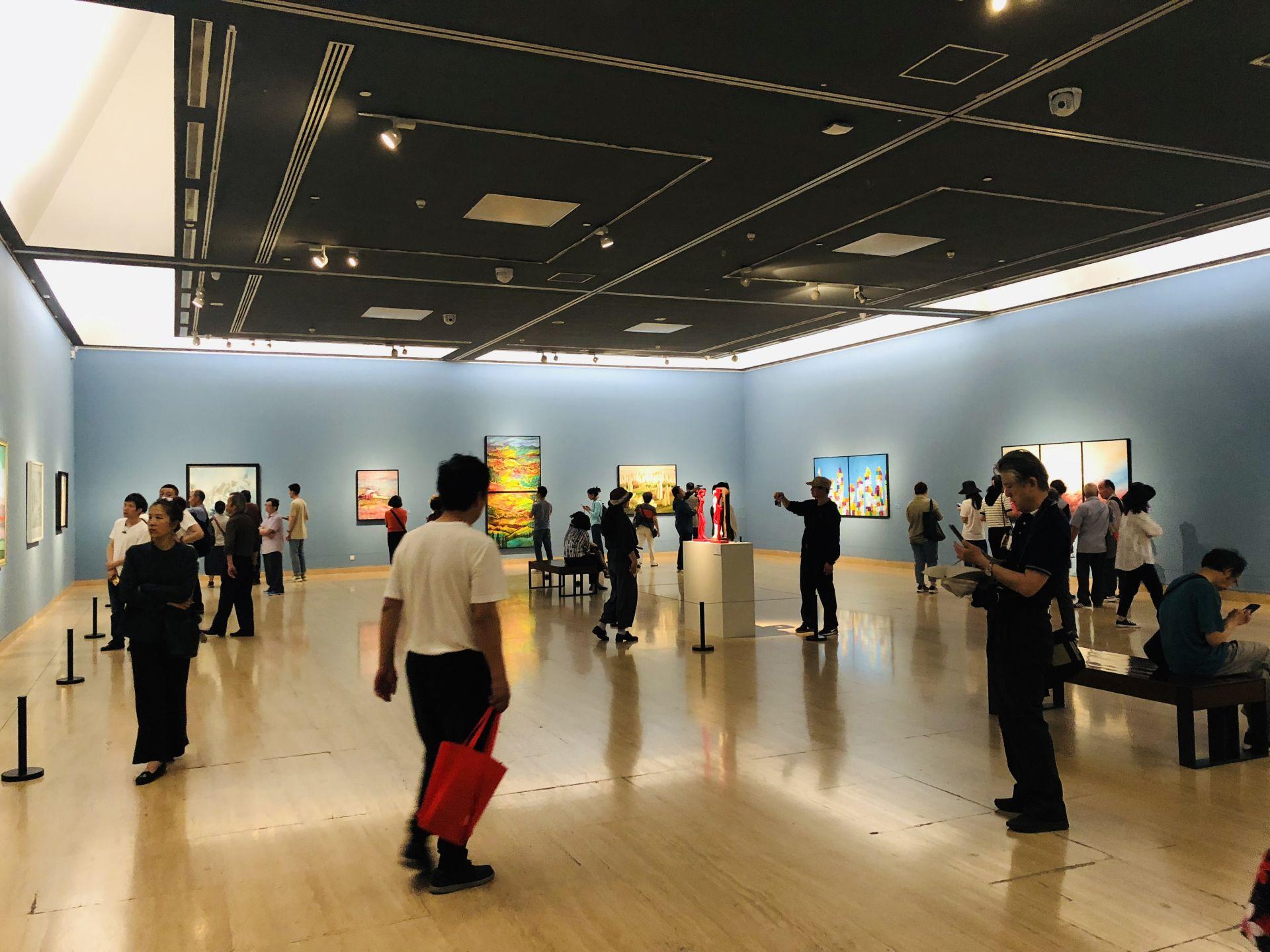"""图为中国美术馆""""大道融通——亚洲艺术作品展""""美丽中国主题展厅,游客在欣赏艺术作品"""