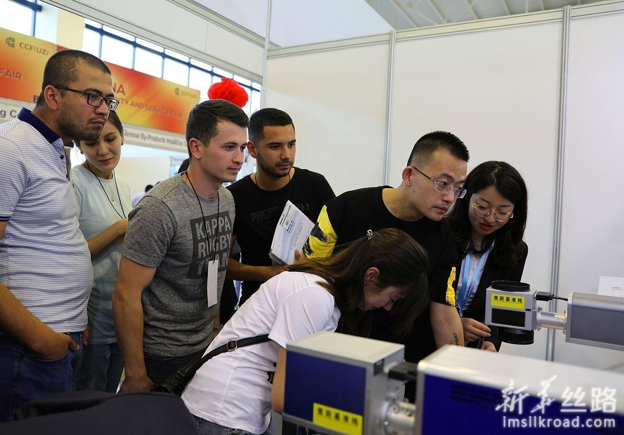 6月12日,在乌兹别克斯坦首都塔什干国家会展中心,中方参展商在为乌方人员展示设备操作。新华社记者 蔡国栋 摄