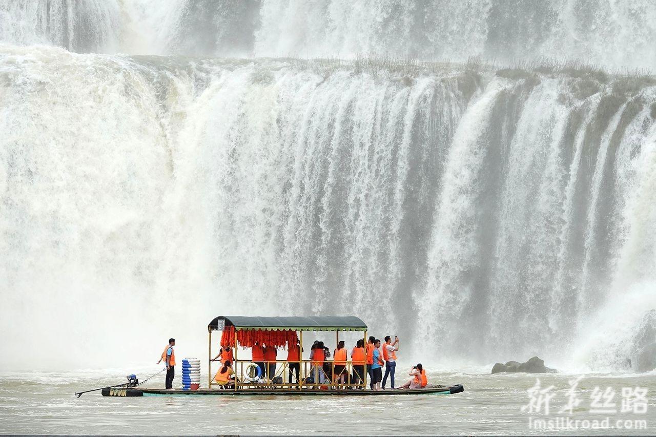 6月11日,游人乘坐竹筏观赏德天瀑布。新华社发(喻湘泉 摄)