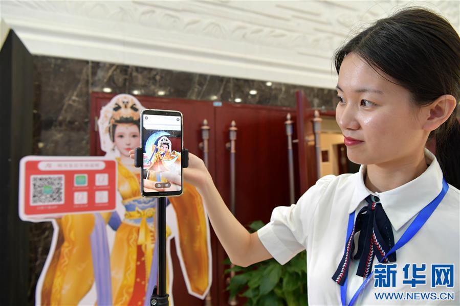 6月4日,在宜春市明月山温汤镇智慧旅游展厅,游客使用手机查看知名景点。 新华社记者 彭昭之 摄