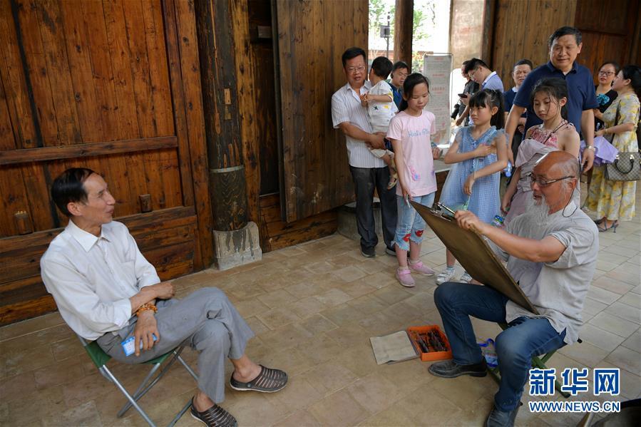 6月5日,在江西省宜春市万载县万载古城,画师在给游客画肖像。 新华社记者 彭昭之 摄