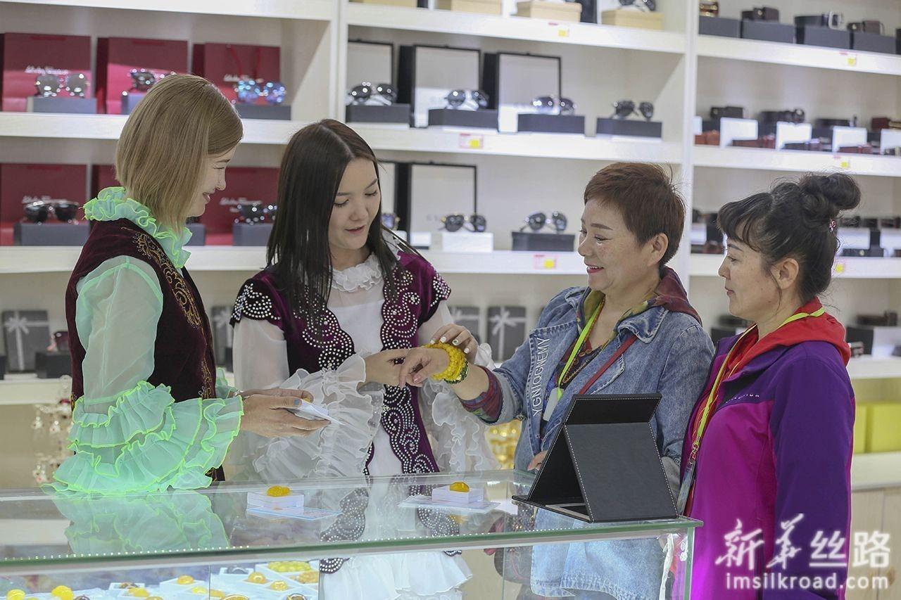 6月12日,哈萨克斯坦姐妹高孜雅(左一)、丽娜(左二)在中哈霍尔果斯国际边境合作中心向中国旅客介绍哈萨克斯坦特色首饰。新华社发(周旭 摄)