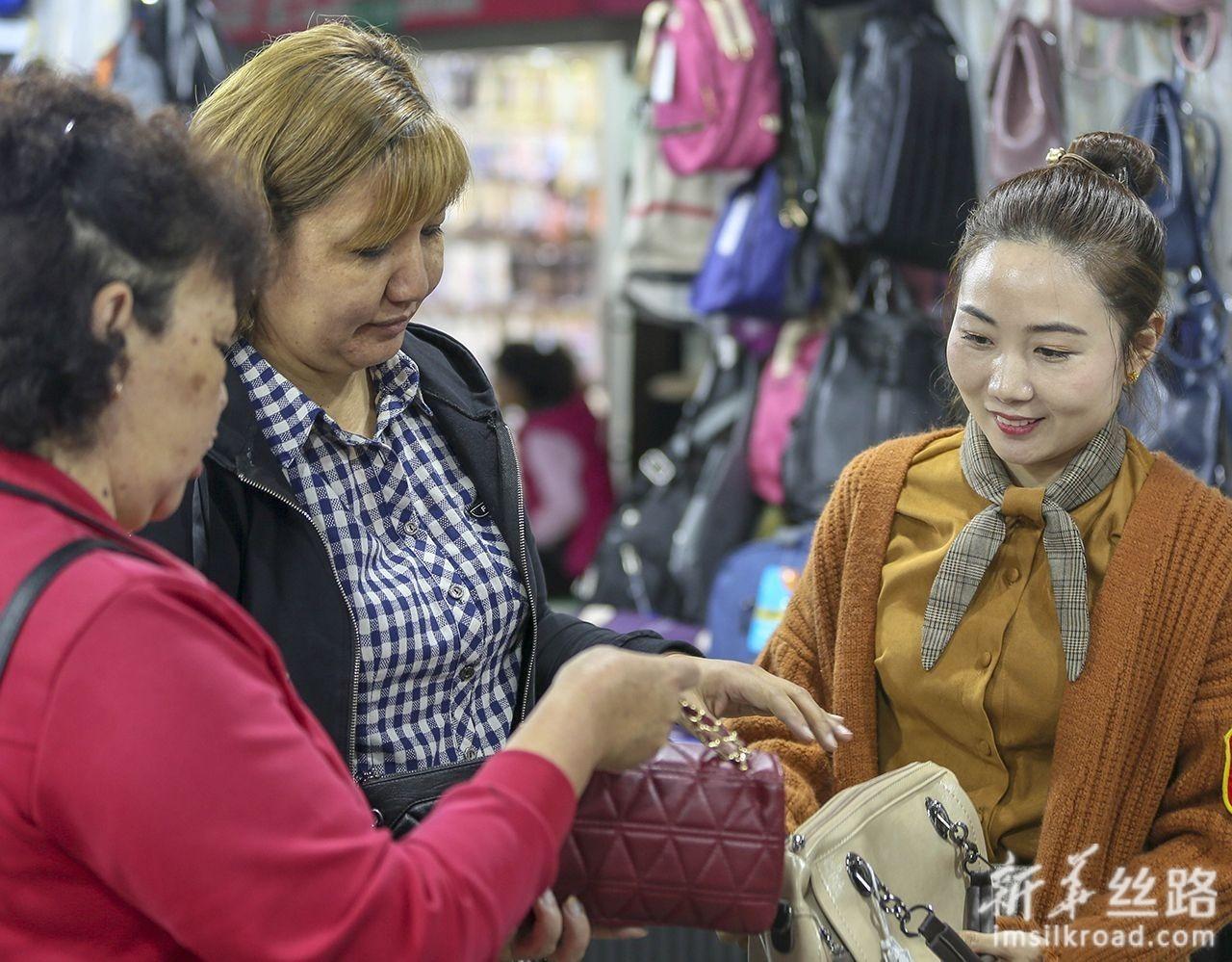 6月12日,哈萨克斯坦商人玛雅(中)在中哈霍尔果斯国际边境合作中心黄金口岸商城了解箱包批发价格。新华社发(周旭 摄)