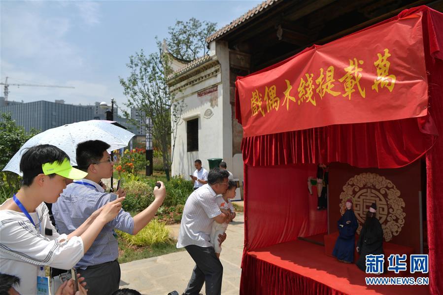 6月5日,游客在江西省宜春市万载县万载古城观看提线木偶戏。 新华社记者 彭昭之 摄