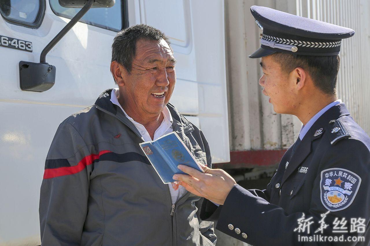6月11日,伊尔克什坦出入境边防检查站执勤民警向吉尔吉斯斯坦驾驶员介绍出入境有关事宜。新华社发(罗阳 摄)