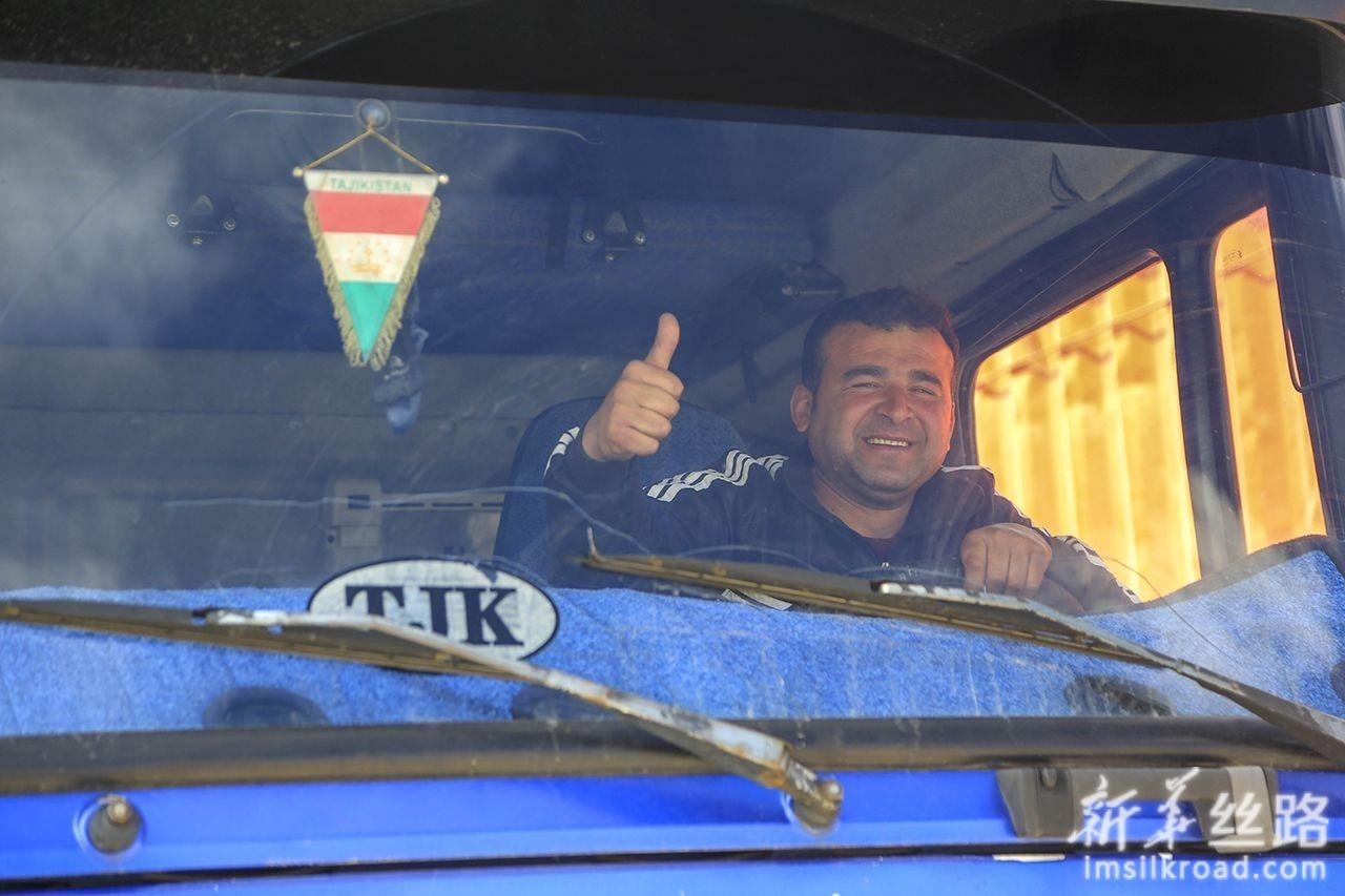 6月11日,在中塔卡拉苏口岸,等待入境的塔吉克斯坦司机竖起拇指打招呼。新华社发(黄欢 摄)