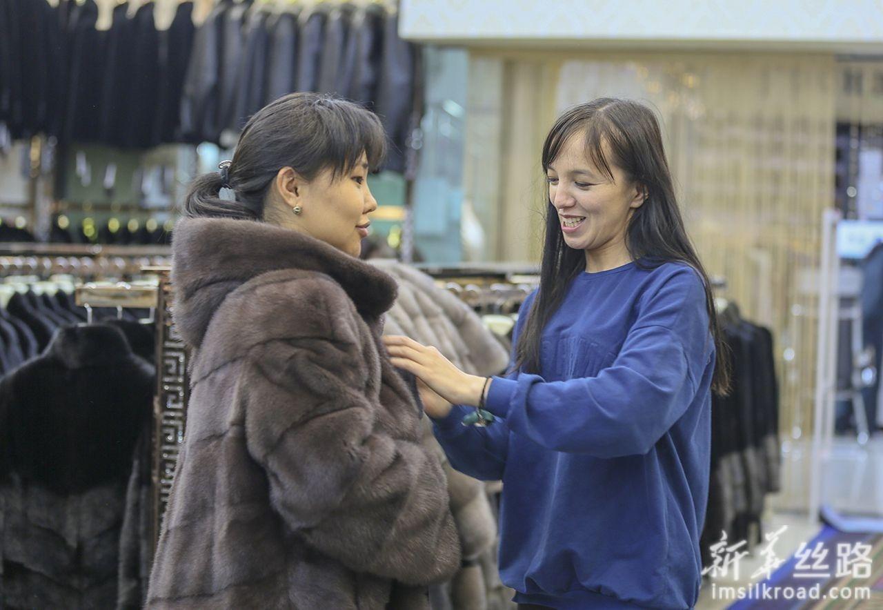 6月12日,哈萨克斯坦商人阿伊努拉(右)在中哈霍尔果斯国际边境合作中心帮顾客试衣。新华社发(周旭 摄)