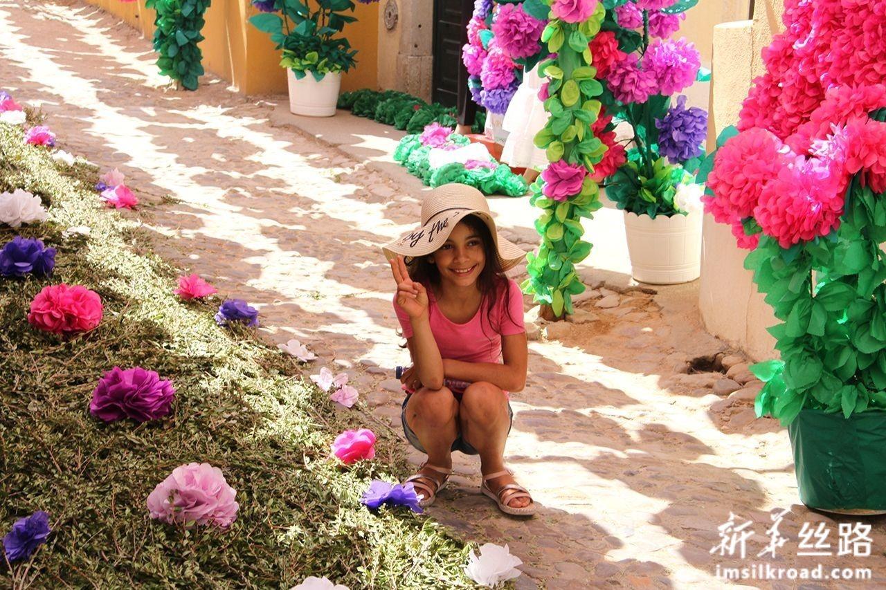 7月6日,在葡萄牙托马尔市,一名女孩参加托盘节庆祝活动时留影。新华社记者 温新年 摄