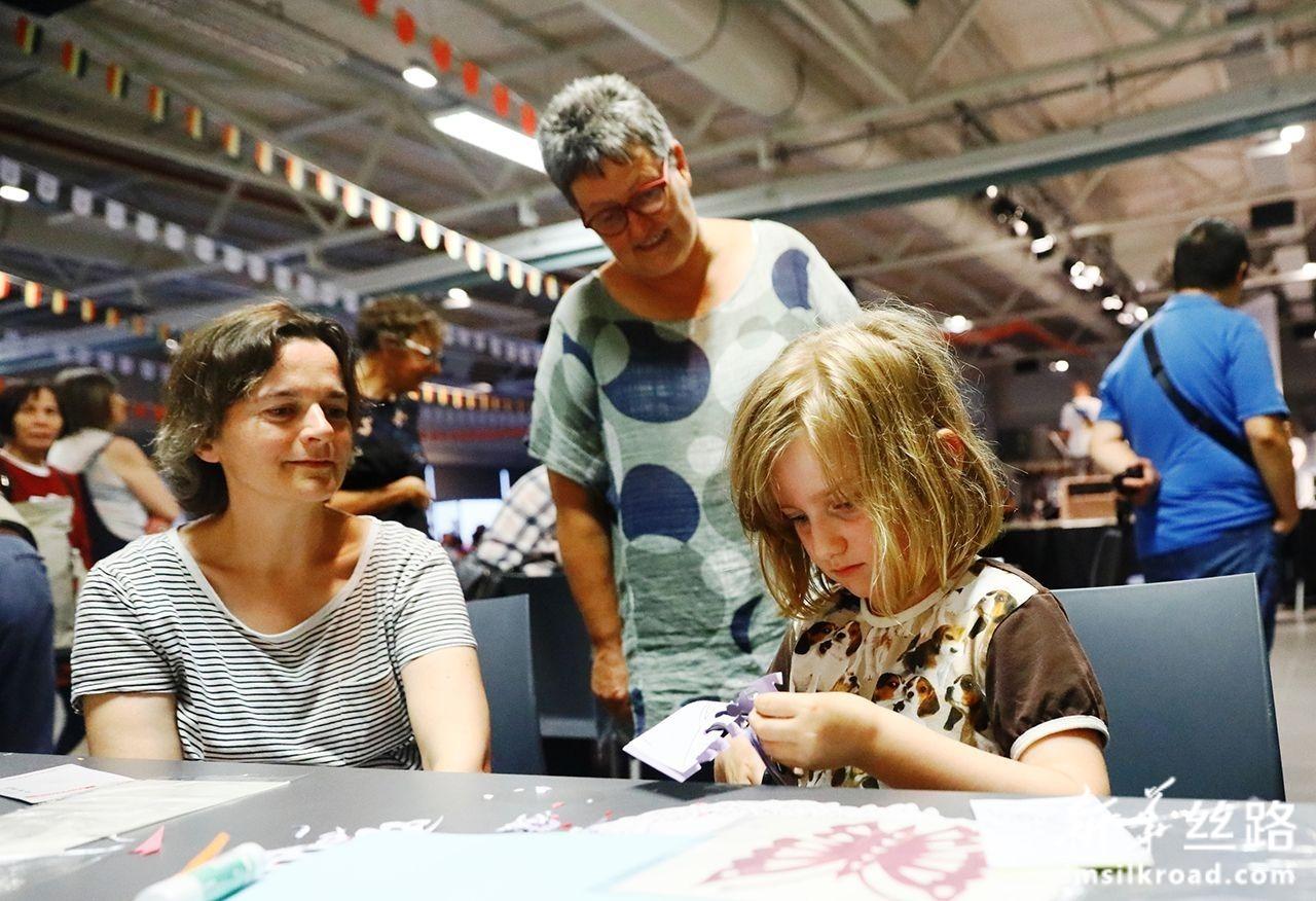 7月27日,在比利时赞德霍芬,一名比利时小朋友体验中国剪纸。潘革平