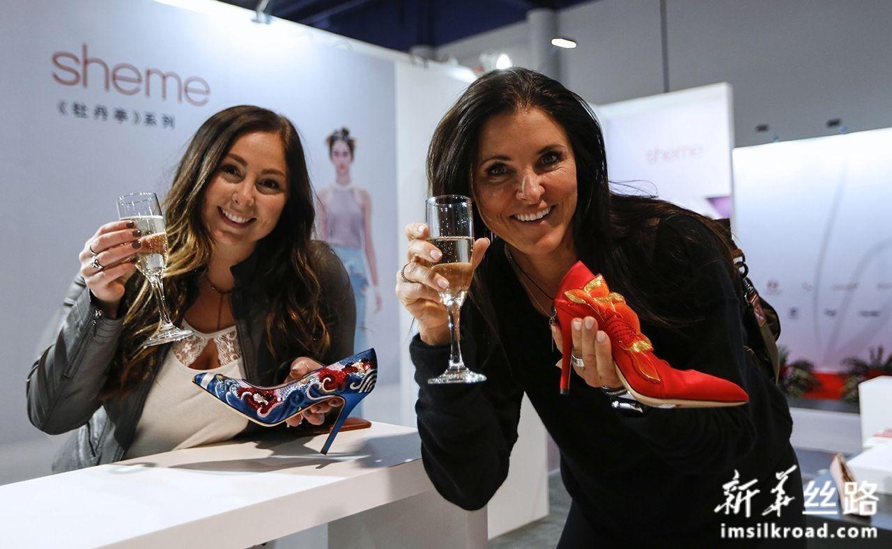8月12日,在美国拉斯维加斯,两名顾客参加中国鞋类品牌推广活动。新华社记者 李颖 摄