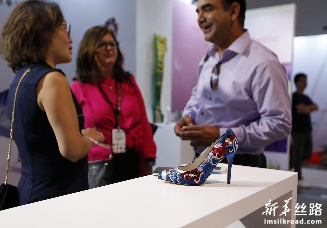 8月12日,在美国拉斯维加斯,顾客在中国鞋类品牌推广活动上交谈。新华社记者 李颖 摄