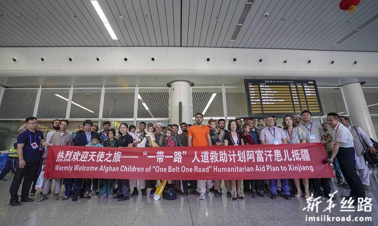 7月31日,在乌鲁木齐地窝堡国际机场,中国红十字会等有关部门与来自阿富汗的先心病患儿及家属合影留念。新华社记者 赵戈 摄