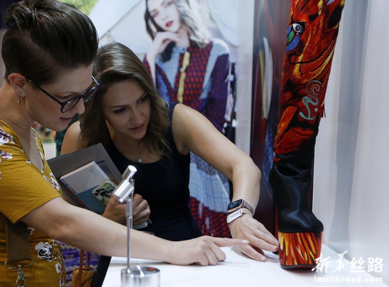 8月12日,在美国拉斯维加斯,两名嘉宾在中国鞋类品牌推广活动上观看展品。新华社记者 李颖 摄