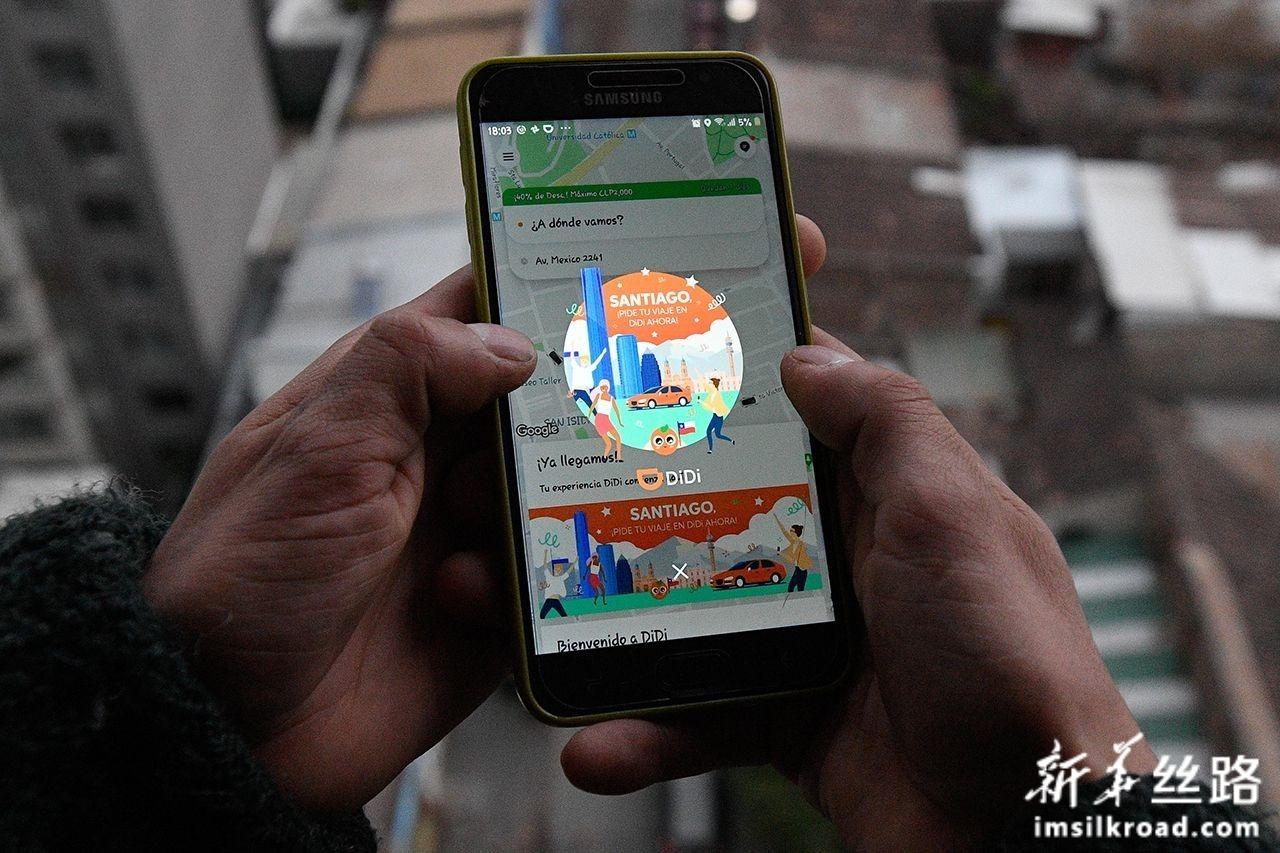 8月6日,在智利首都圣地亚哥,一名用户在手机上使用滴滴出行软件。新华社发(豪尔赫·比列加斯摄)