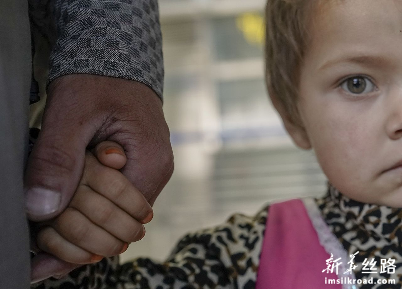 7月31日,在乌鲁木齐地窝堡国际机场,一位等待治疗的阿富汗先心病患儿紧紧抓住父亲的手。新华社记者 赵戈 摄